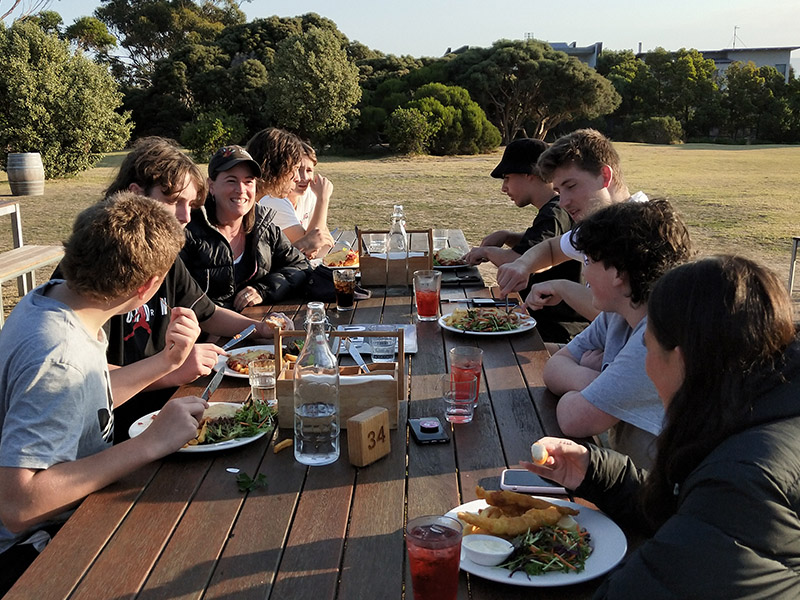 Students eating at a picnic table with their teacher