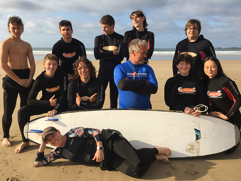 Students and their teacher posing with the surf instructor and a surfboard