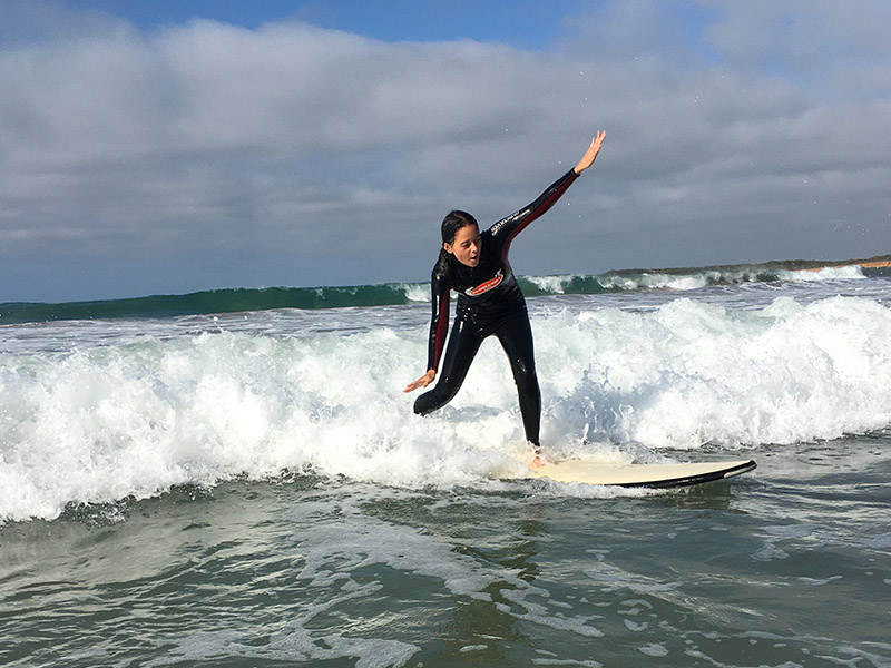 Student standing up on a surfboard riding a wave
