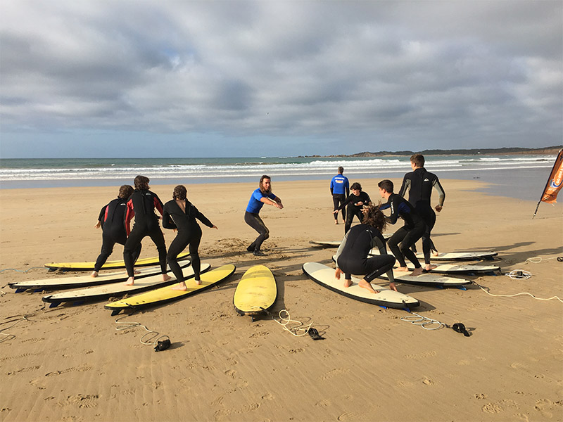 Instructor teaching students to surf by practicing standing on surfboards on the sand