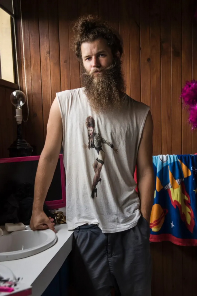 Photo of Artist Daniel Newell. Daniel is leaning on the basin in a wood panelled bathroom looking directly at the camera. Daniel is wearing a white T-shirt with the sleeves cut off with the image of a dancer on it.